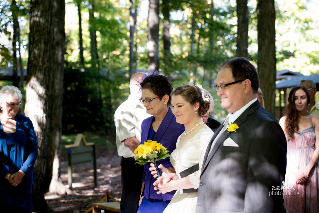 bride coming down aisle in woods