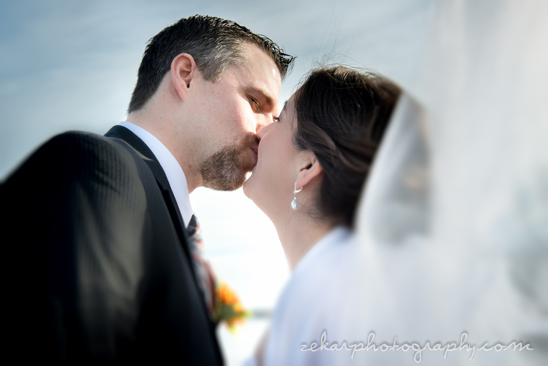 bride and groom kissing in wind