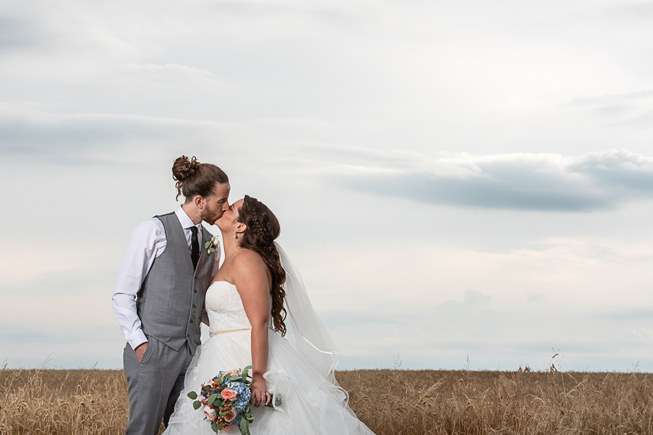 bride groom kissing in front of field