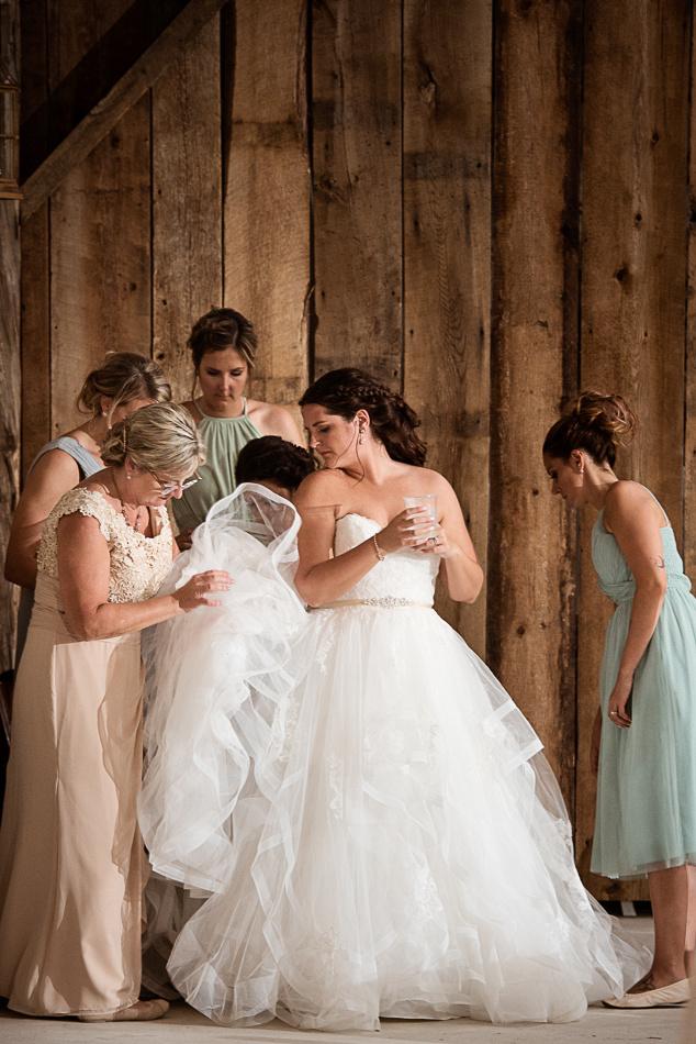bride getting dress bustled