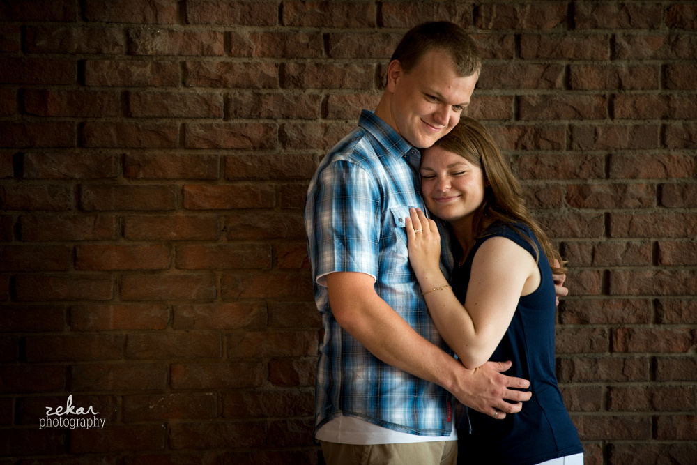 couple cuddling in front of brick wall
