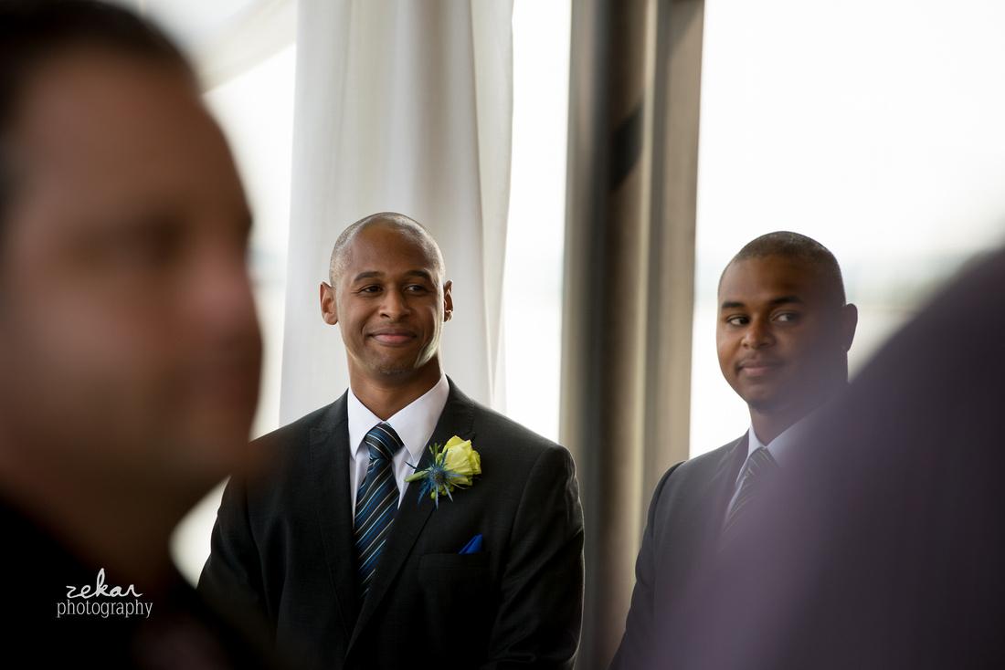 groom looking at bride coming down aisle