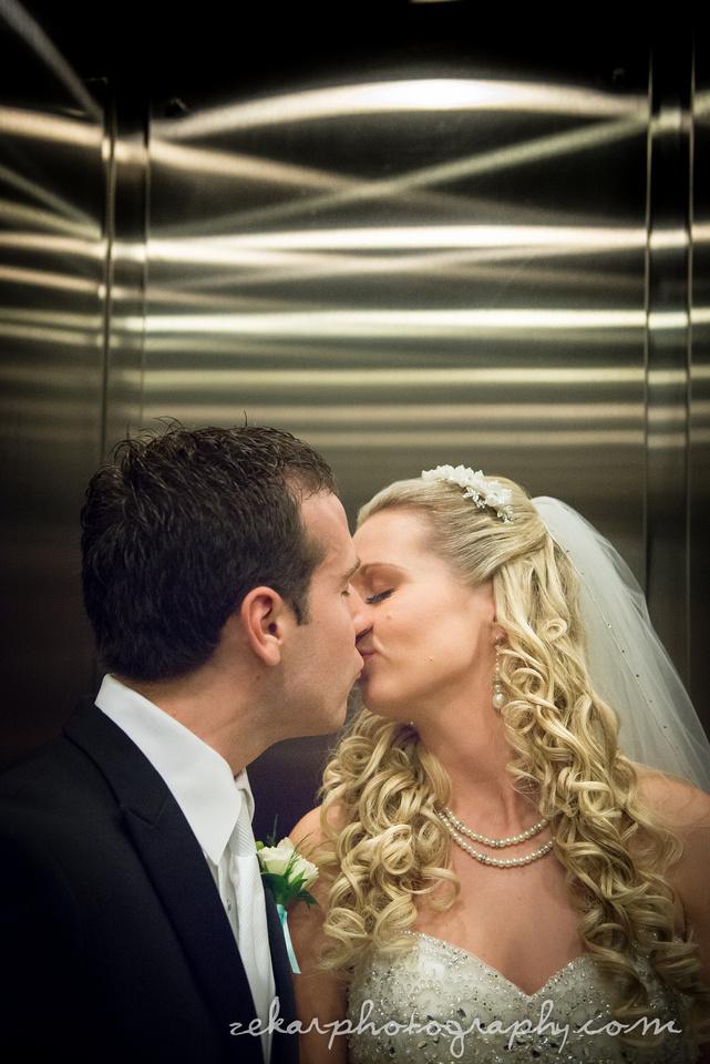 bride and groom kissing in elevator