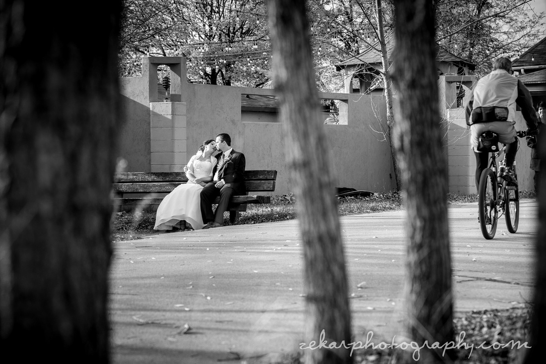 black and white photo of bride and groom on the bench