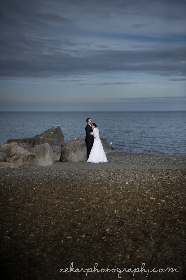 bride and groom on beach on cloudy day