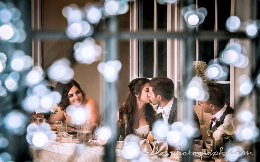 bride and groom kissing through christmas lights at head table at night