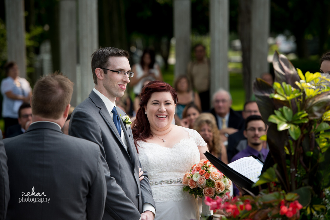 bride and groom smiling at altar