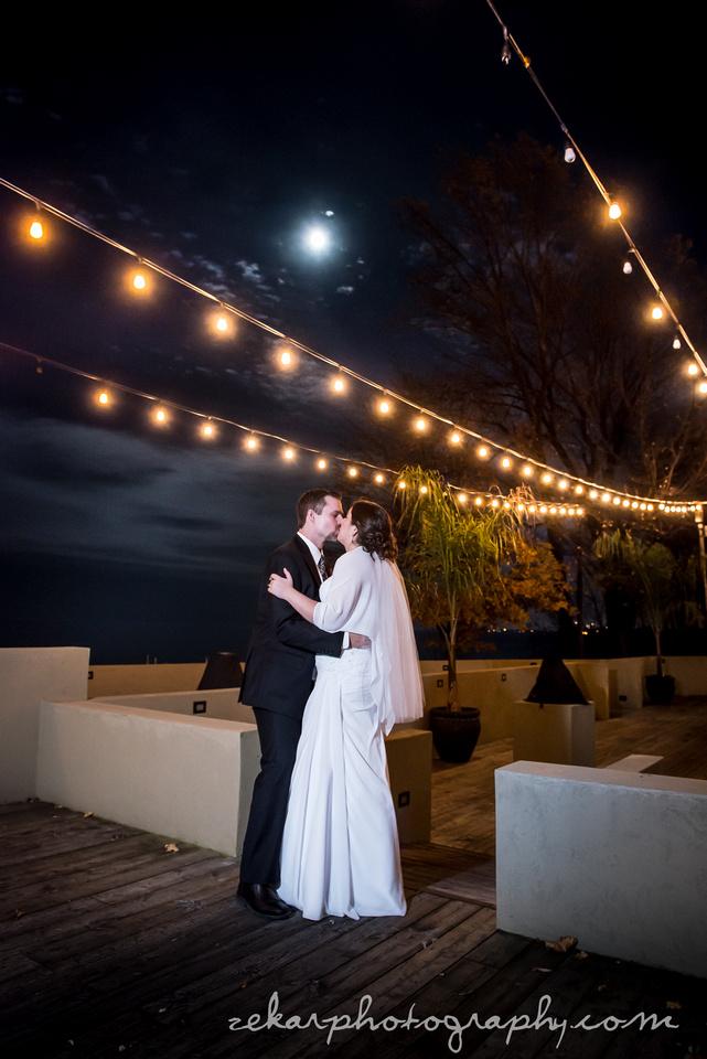 bride and groom kissing at night