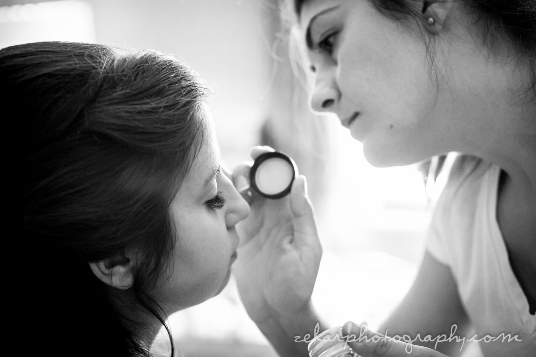 black and white photo of bride getting makeup applied