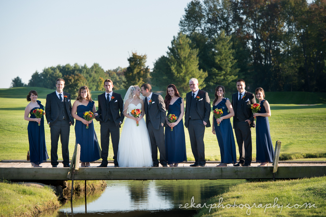 bridal party posing on bridge