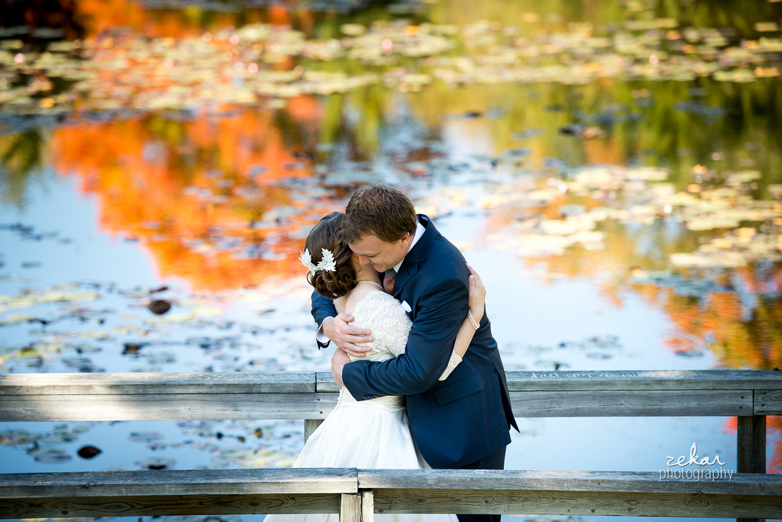 bride and groom hugging by water
