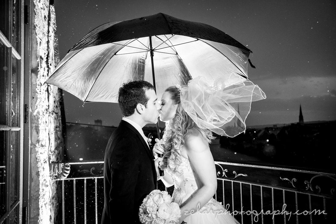 bride and groom kissing in rain