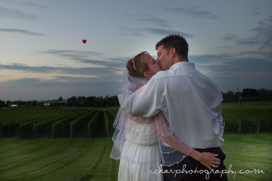 bride and groom watching heart lantern float away