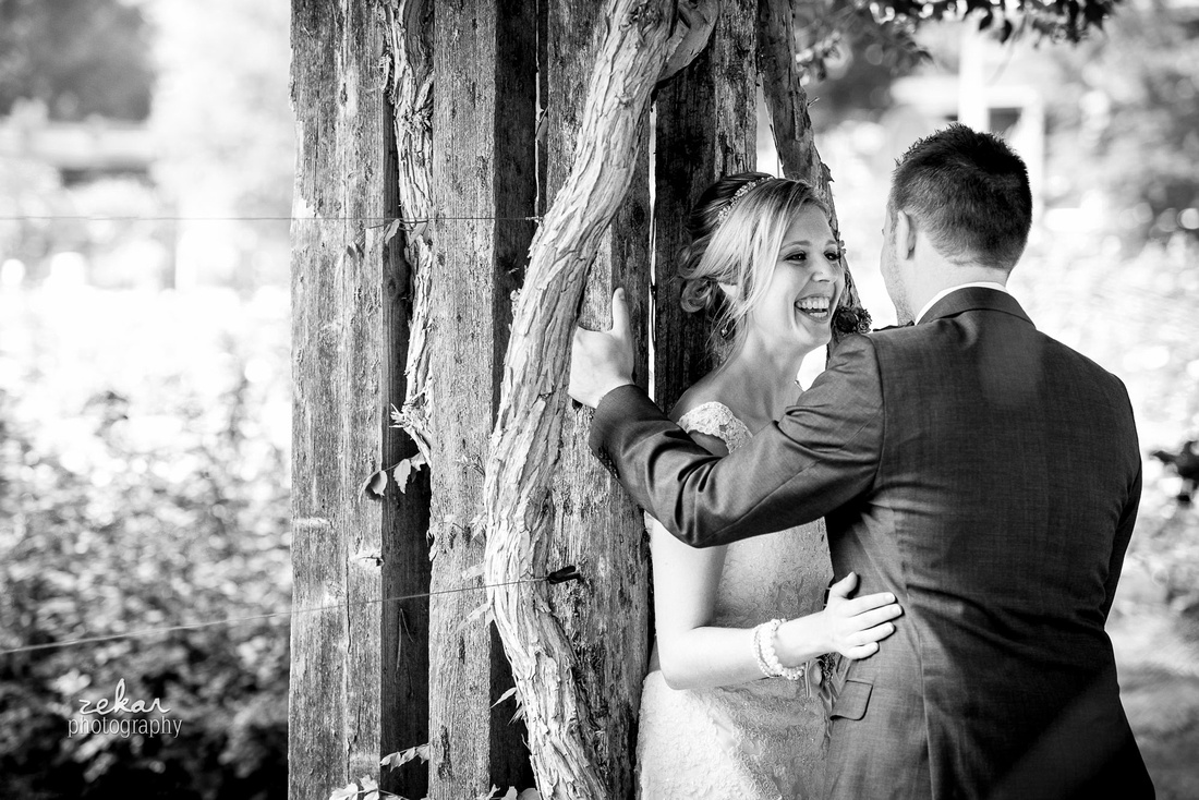 bride and groom kissing by vines