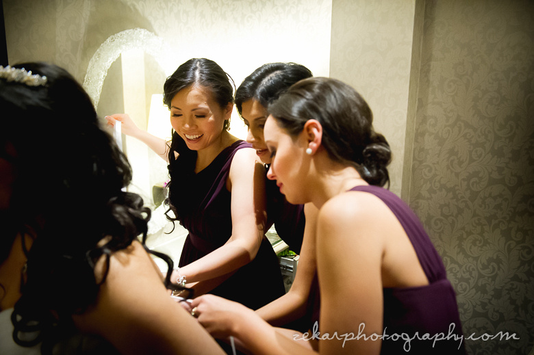 bridal party helping with wedding dress
