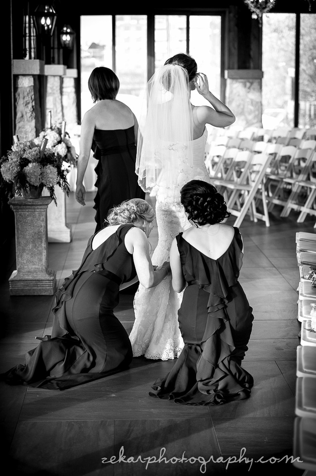 bridesmaids bustling up bridal gown