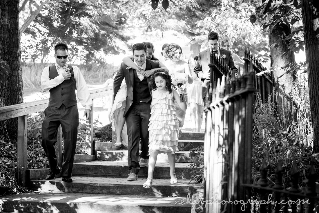 black and white photo of bride and groom walking with wedding party