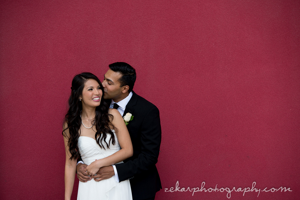 bride and groom on red background kissing
