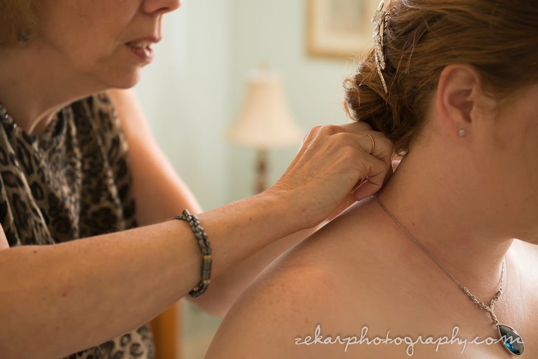 mom putting necklace on bride