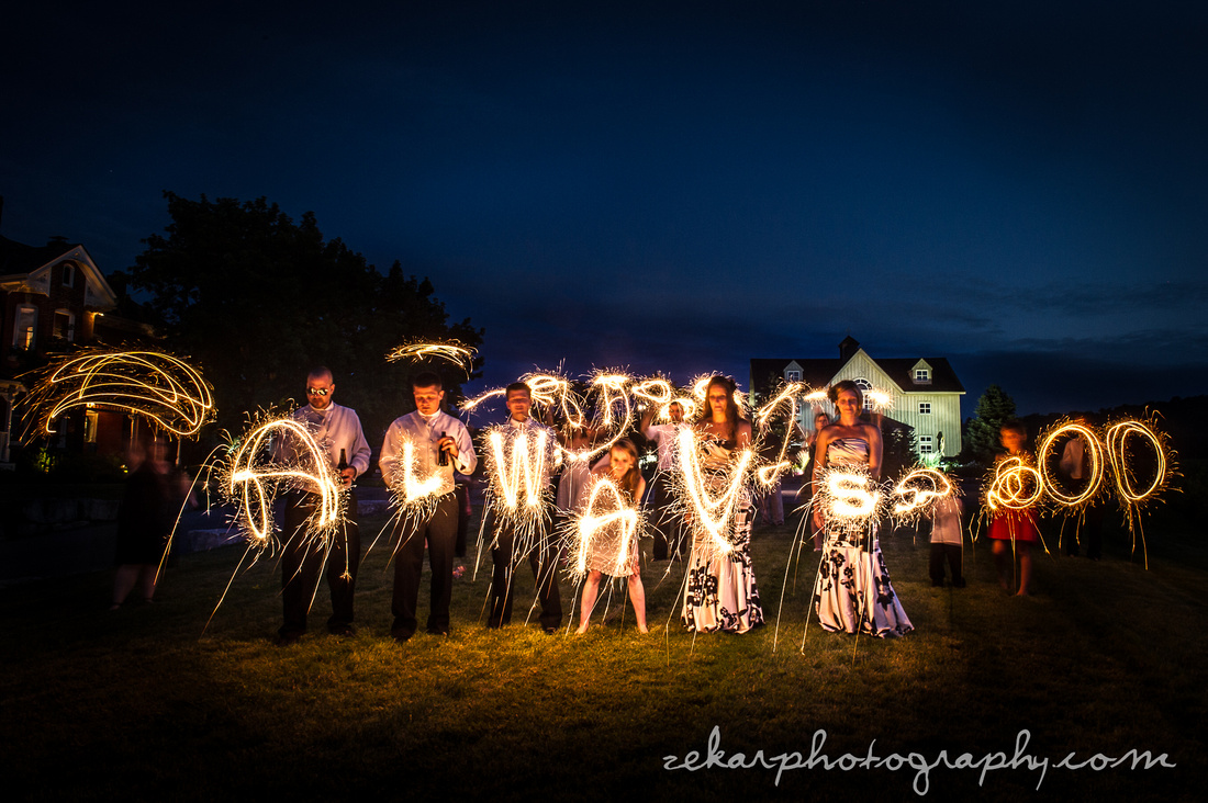 bridal party with sparklers at night
