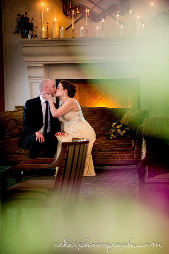 bride and groom kissing on couch