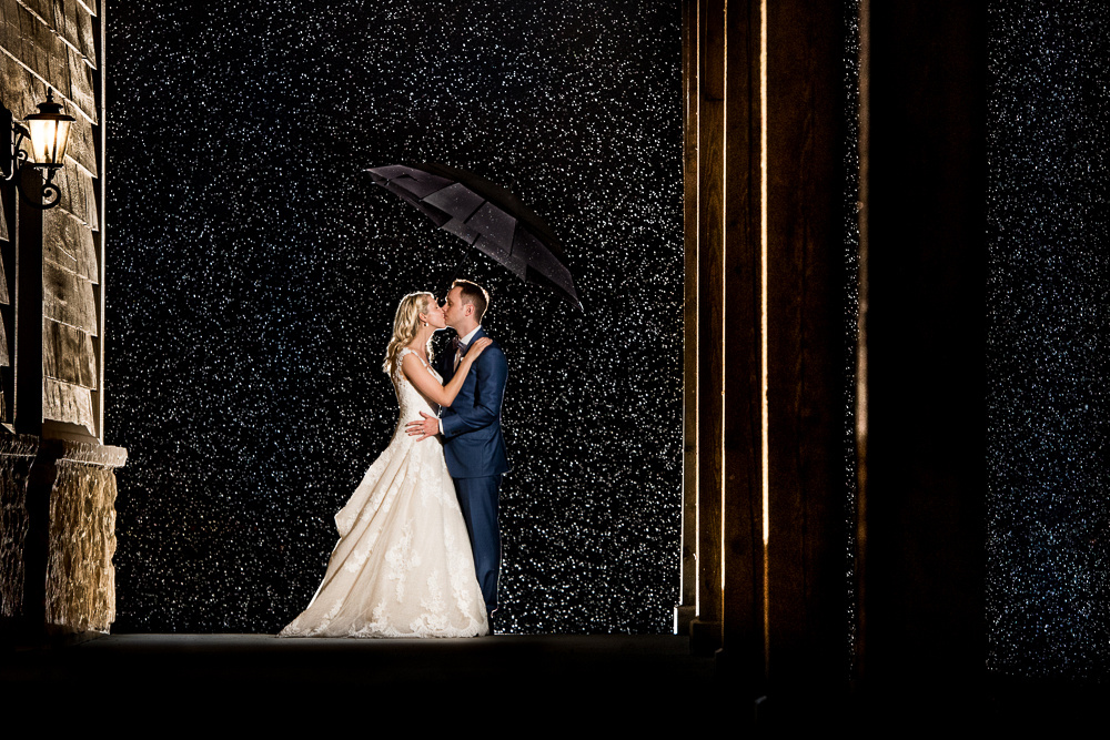 bride and groom in rain at night