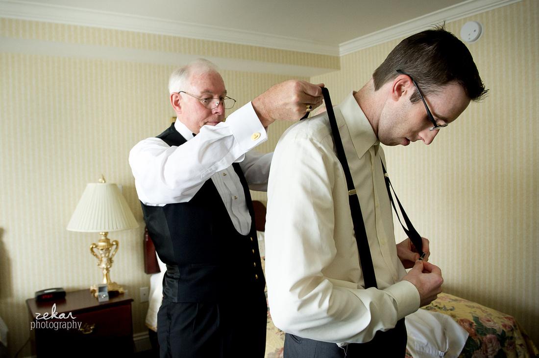 groom getting suspenders on