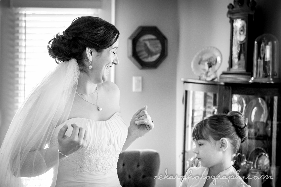 bride laughing at flower girl black and white photo