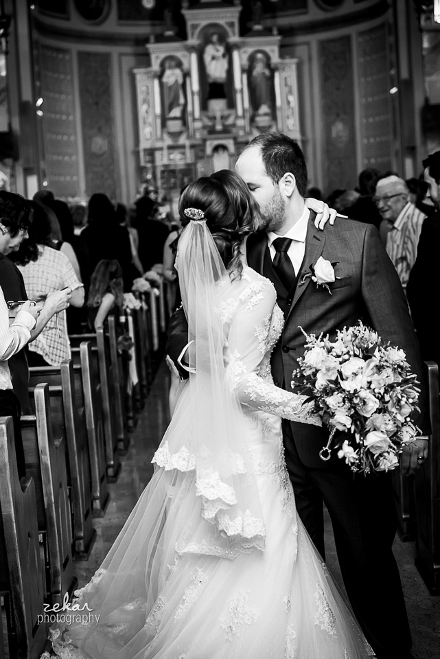 bride and groom kissing in aisle