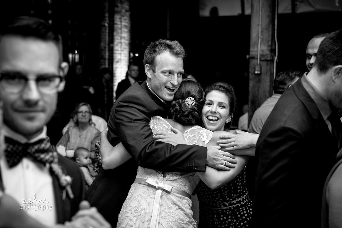 friends hugging bride at reception