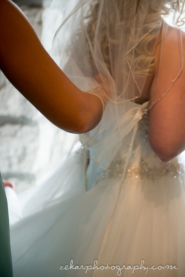 bride getting dress corset done up