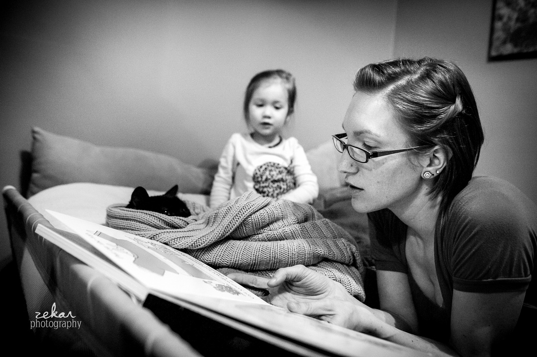 mom reading book to daughter