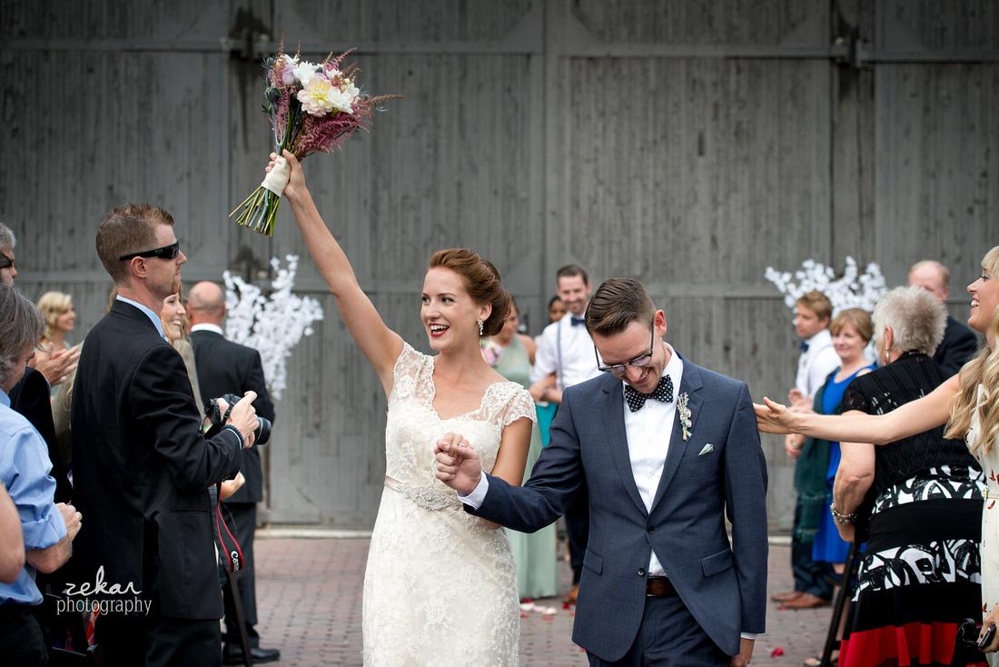 bride and groom cheering down aisle