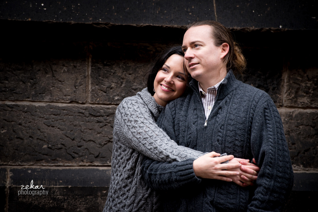 couple in gray sweaters snuggling in front of stone well