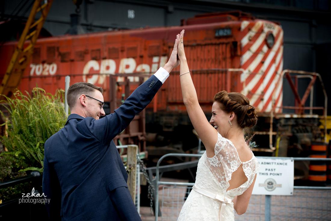 bride and groom high-five beside train