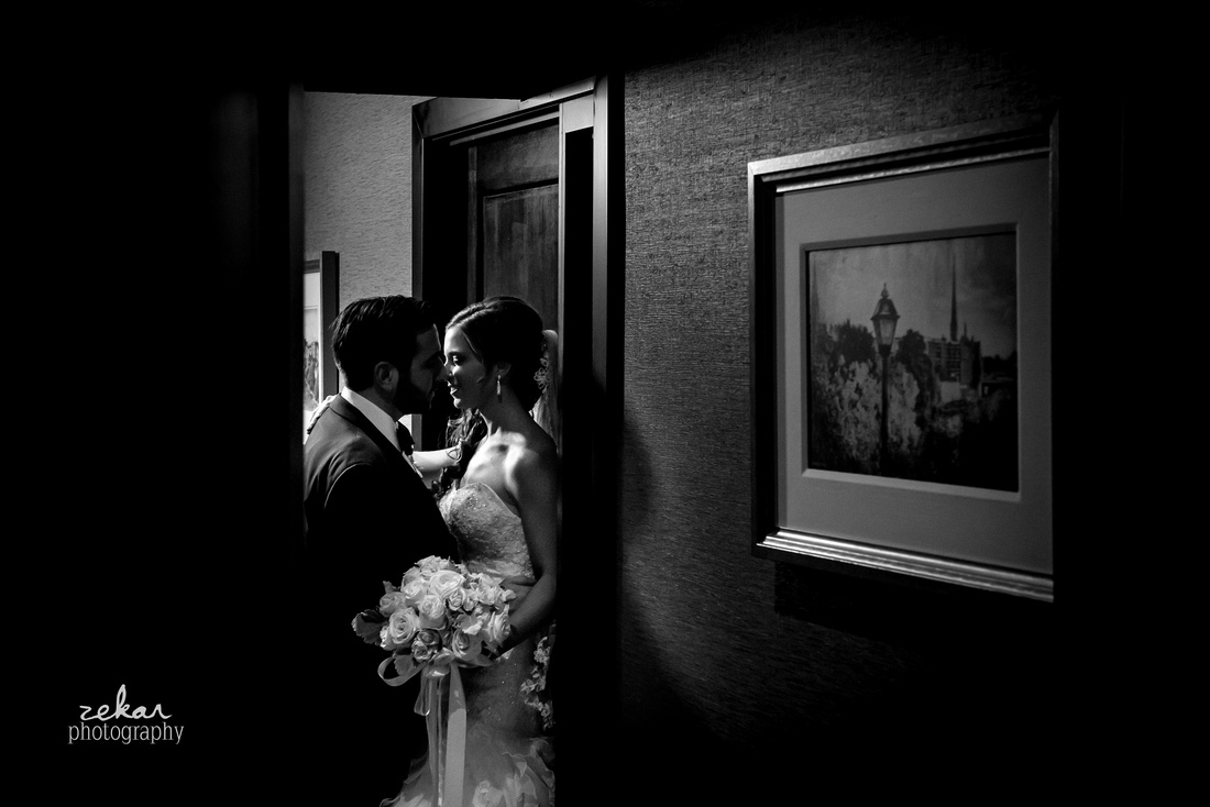 black and white photo of bride and groom kissing in doorway