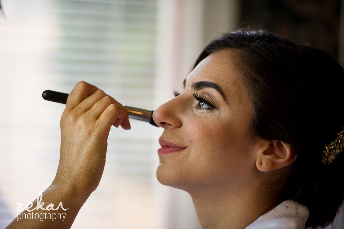 bride getting makeup applied to face