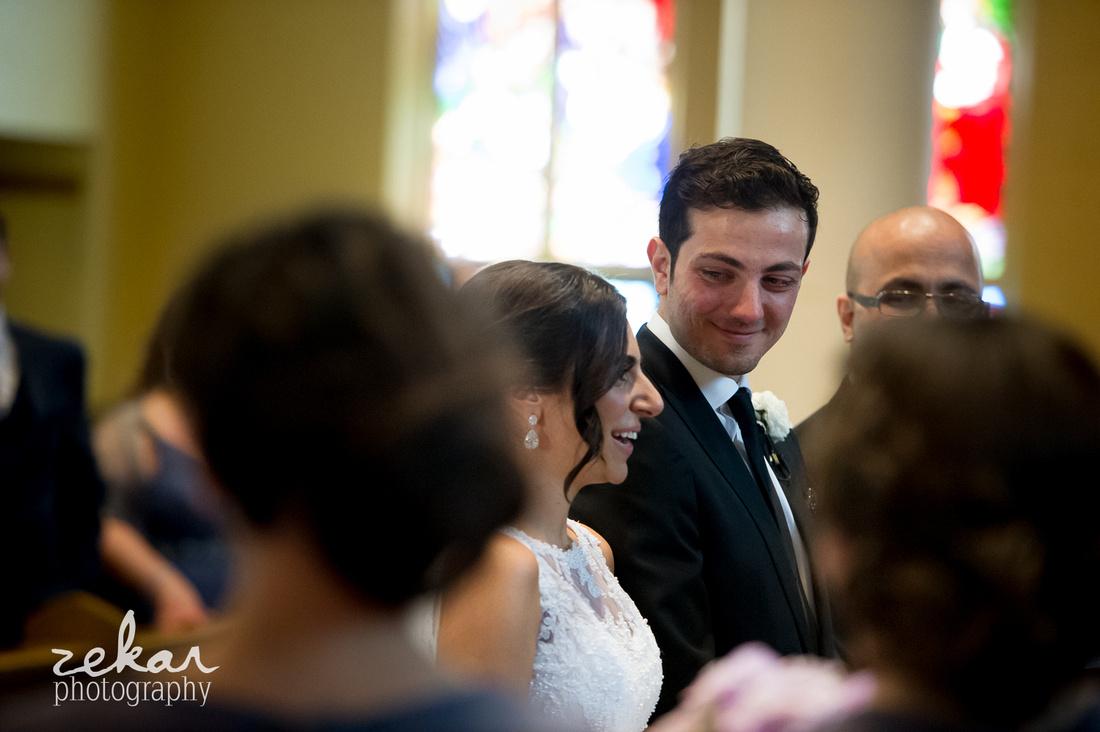 groom smiling at bride at altar
