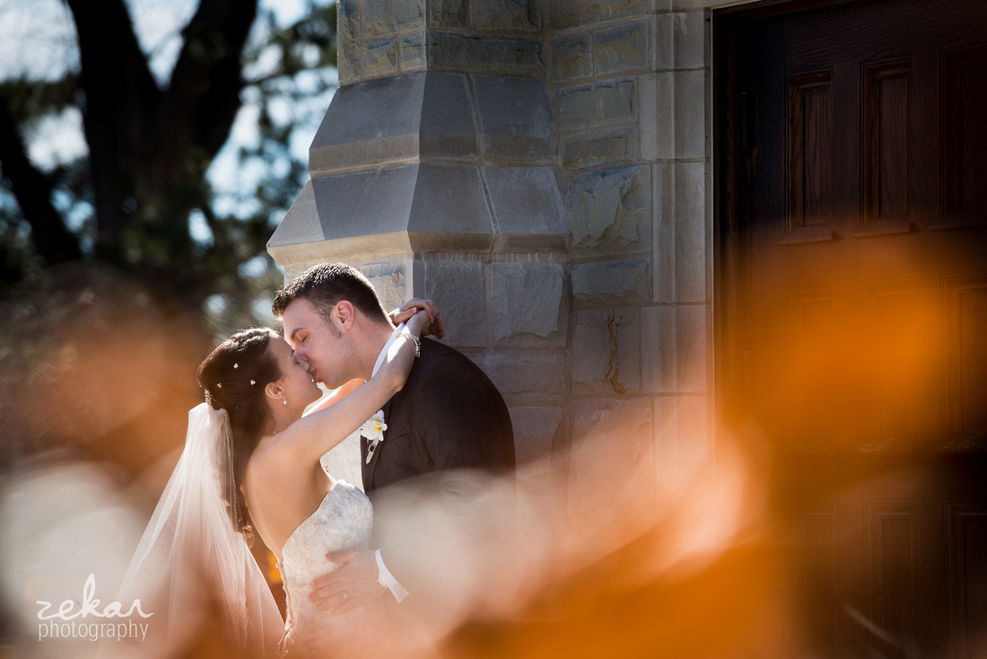 couple kissing outside old church
