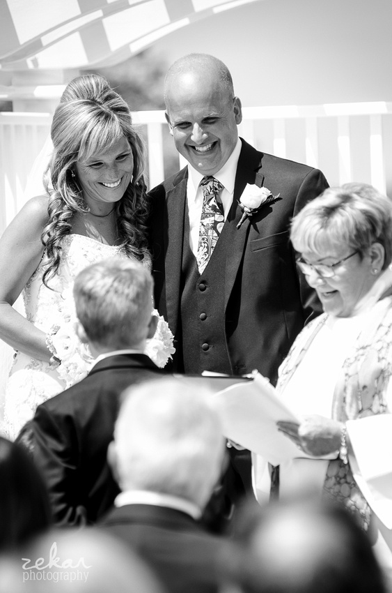 bride and groom smiling at son