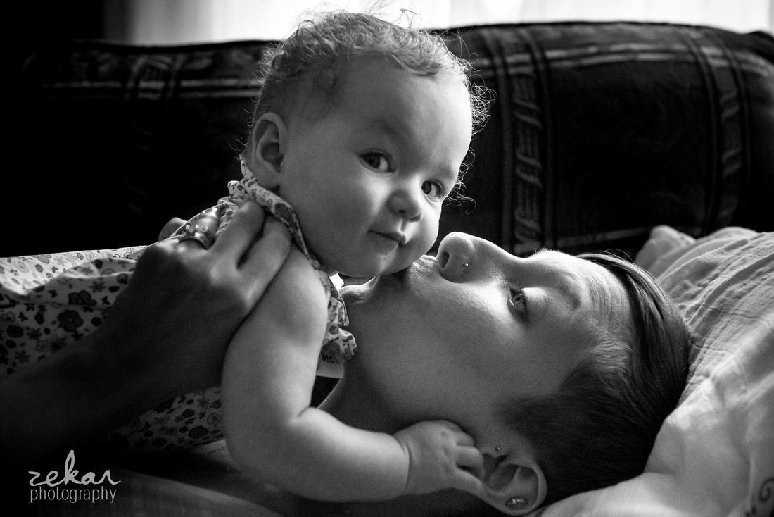 baby looking at camera while mom kisses cheek