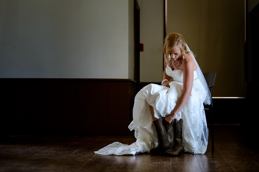 bride putting cowboy boots on bridal gown