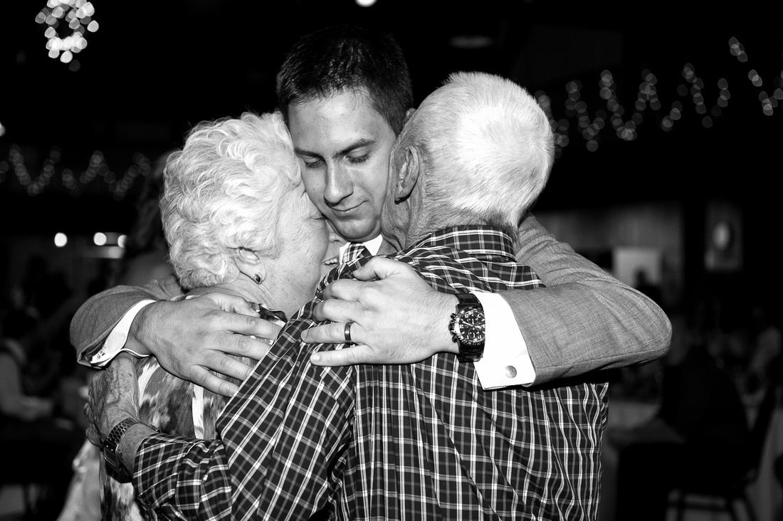 groom hugging both grandparents