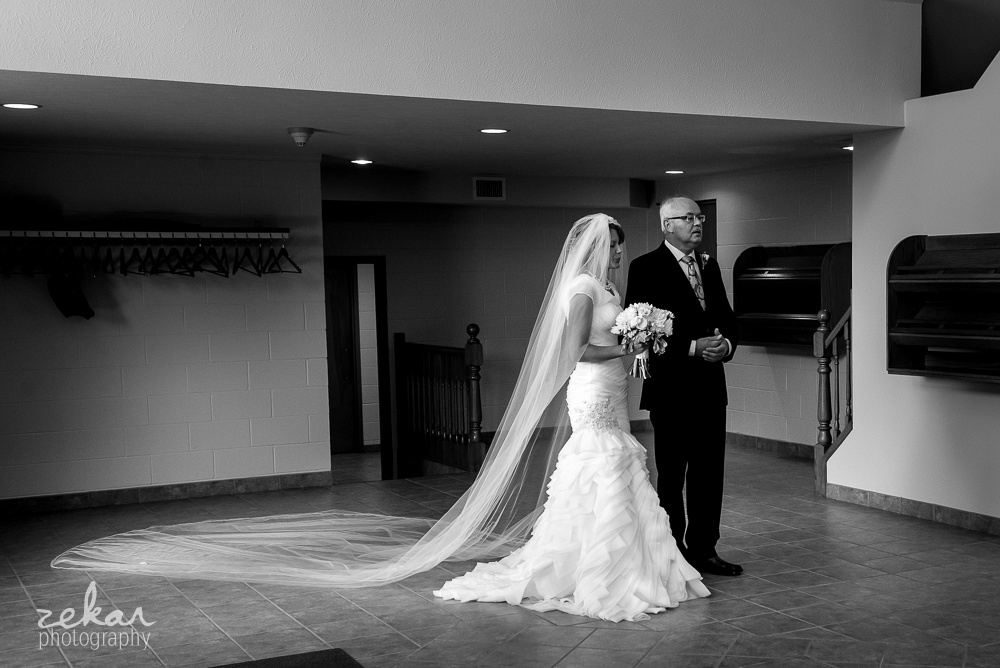 bride waiting to go down aisle with father