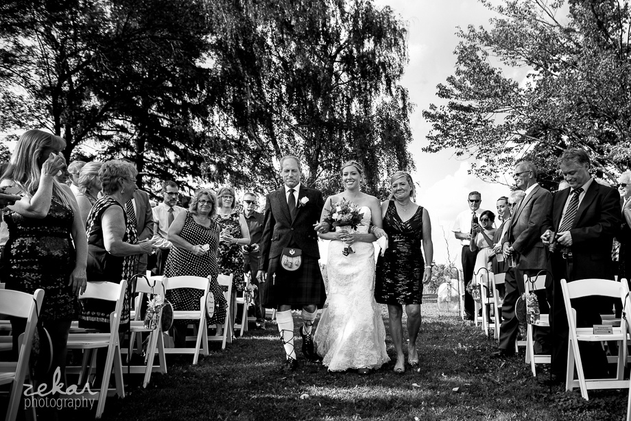 bride walking down aisle with parents
