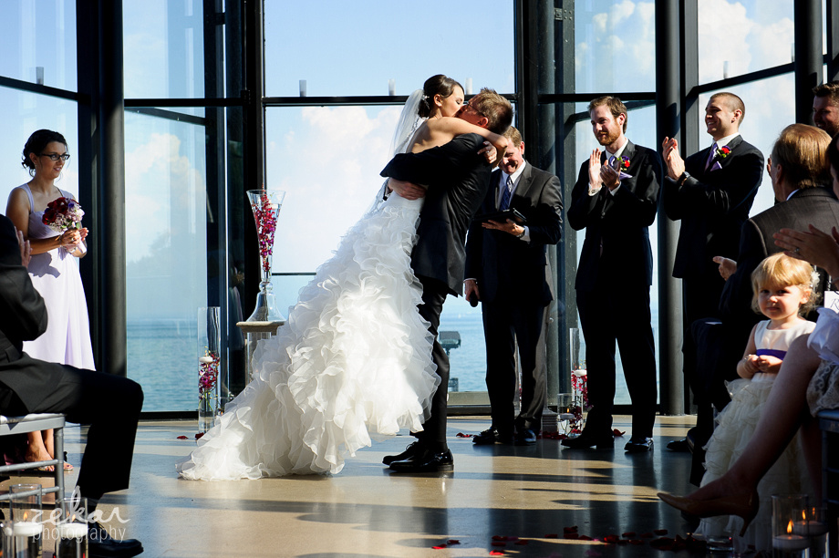 groom lifts bride up at altar