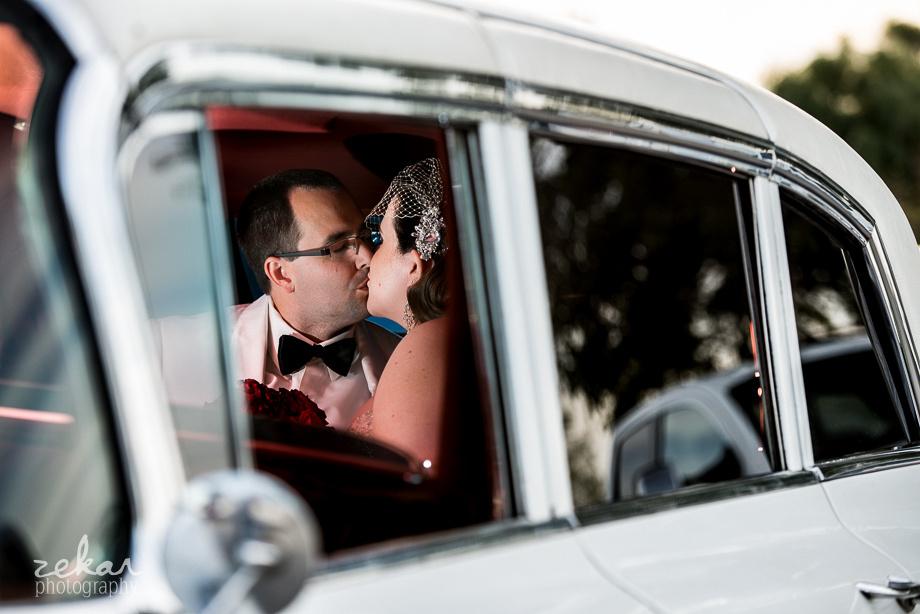 bride and groom kissing in fancy car