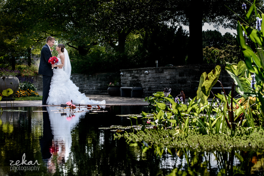 bridal couple next to koi pond