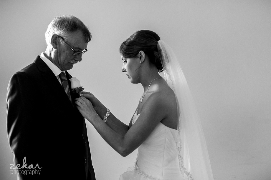bride pinning corsage onto dads lapel