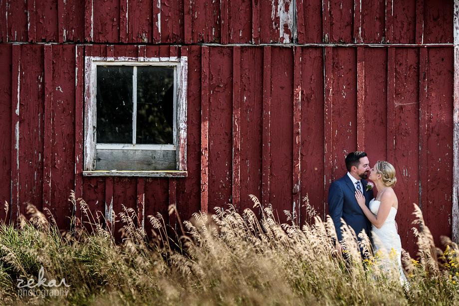 couple kissing beside red barn